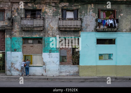 Two men look through an open ground floor window of an apartment block in Havana, Cuba. A woman above looks out - Stock Photo