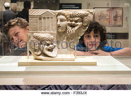 Two boys at the Royal Ontario Museum standing beside a marble slab sculpture depicting faces of a young woman and - Stock Photo