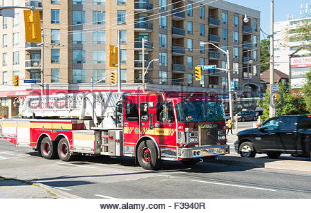 Fire engine of the Toronto Fire Services moving on road. The vehicle is red in color with white hydraulic ladder - Stock Photo