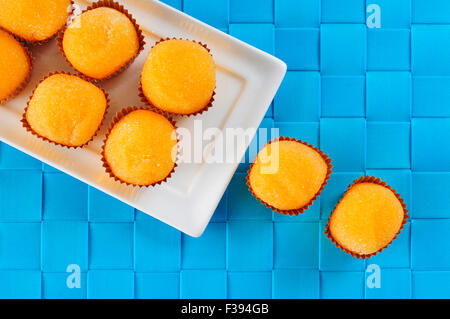 high-angle shot of some yemas de santa teresa, a typical confection of Spain, in a white ceramic tray, on a blue - Stock Photo