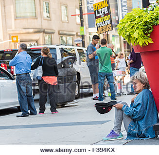 Religion and Hypocrisy: Old destitute woman sitting on the street begging for alms while a Christian man holds a - Stock Photo