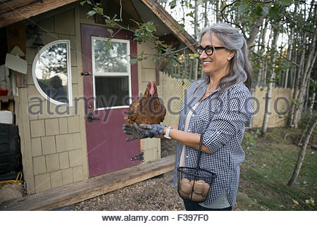 Smiling woman with chicken and eggs in yard - Stock Photo
