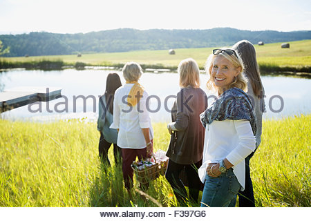 Portrait smiling woman with friends sunny grass lake - Stock Photo