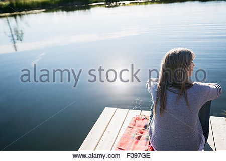 Woman relaxing on dock at sunny lakeside - Stock Photo