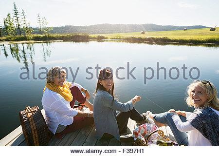 Portrait smiling women enjoying picnic dock sunny lakeside - Stock Photo