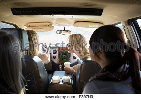 Women drinking coffee inside car - Stock Photo