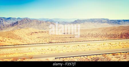 Retro toned panoramic country highway, USA.