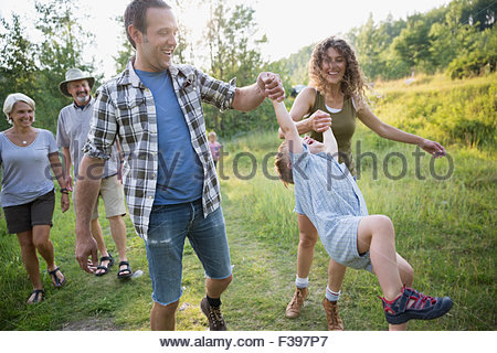 Parents swinging son in woods - Stock Photo
