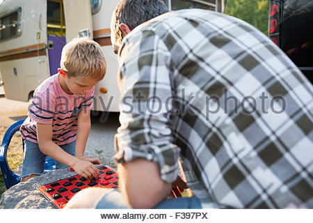 Father and son playing checkers at campsite - Stock Photo