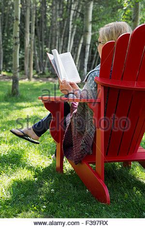 a woman sitting in an adirondack chair on a dock on a lake