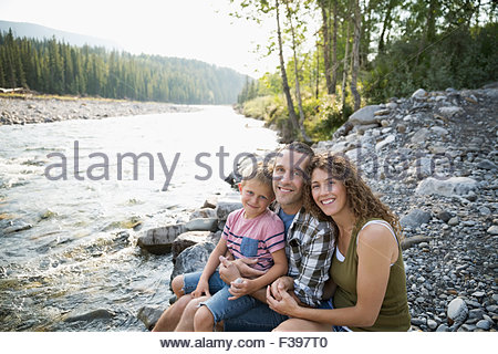 Portrait smiling family at craggy riverside - Stock Photo