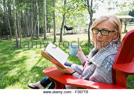 Portrait woman reading book drinking coffee in yard - Stock Photo
