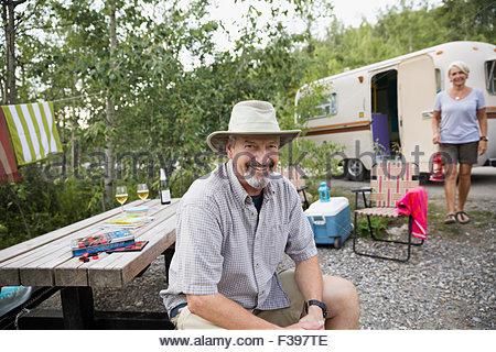Portrait smiling senior man at campsite picnic table - Stock Photo
