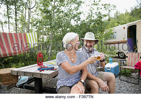 Senior couple toasting wine glasses campsite picnic table - Stock Photo