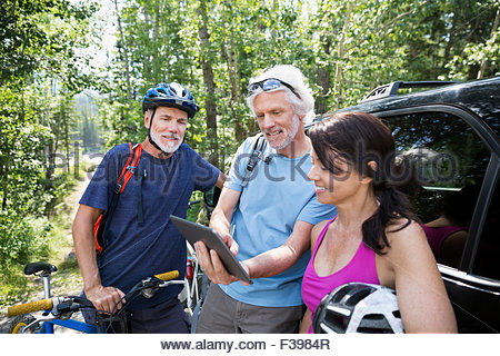 Friends with mountain bike checking digital tablet car - Stock Photo
