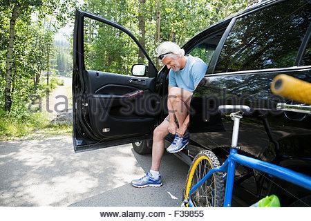 Senior man with mountain bike tying shoelace car - Stock Photo