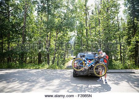 Senior man removing mountain bike from car rack - Stock Photo