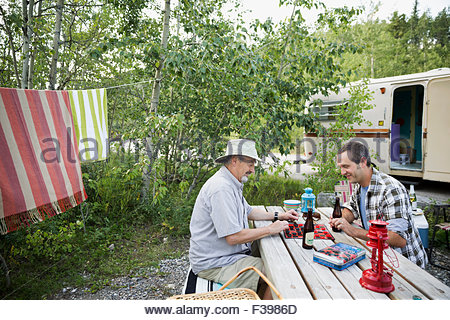 Father and son drinking beer playing checkers campsite - Stock Photo