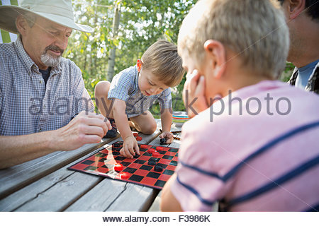 Multi-generation men playing checkers campsite picnic table - Stock Photo