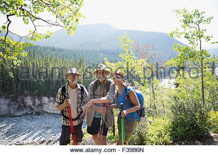 Portrait smiling hikers with poles in sunny woods - Stock Photo