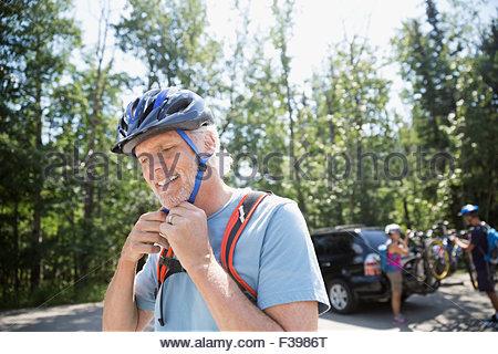 Senior man fastening mountain biking helmet - Stock Photo