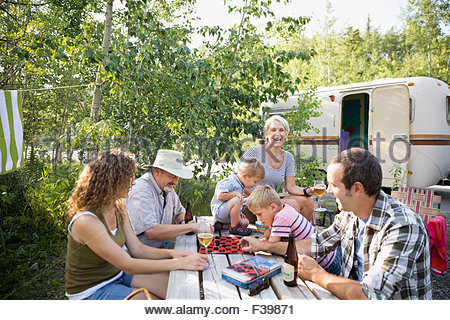 Multi-generation family playing checkers campsite picnic table - Stock Photo