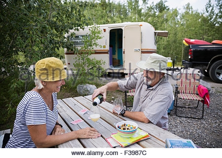 Senior couple drinking sparkling cider campsite picnic table - Stock Photo
