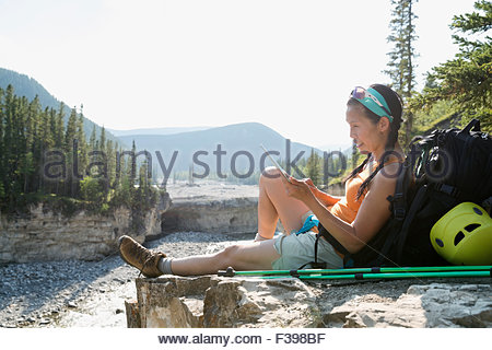 Female backpacker resting with digital tablet on rock - Stock Photo