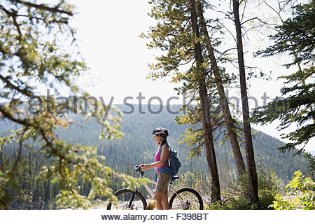 Woman with mountain bike looking view in woods - Stock Photo