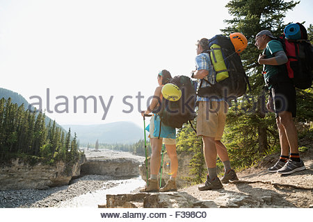 Hikers with backpacks looking at river view - Stock Photo