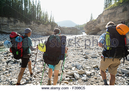 Hikers with backpacks hiking along craggy riverside - Stock Photo