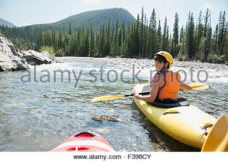 Portrait smiling woman kayaking in river - Stock Photo