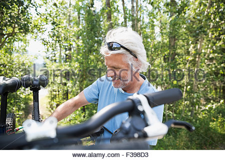Senior man removing mountain bike from rack - Stock Photo