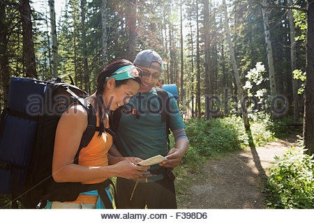 Backpackers checking map on trail in woods - Stock Photo