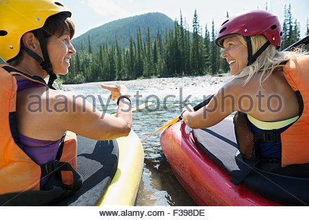 Women in kayaks talking in river - Stock Photo