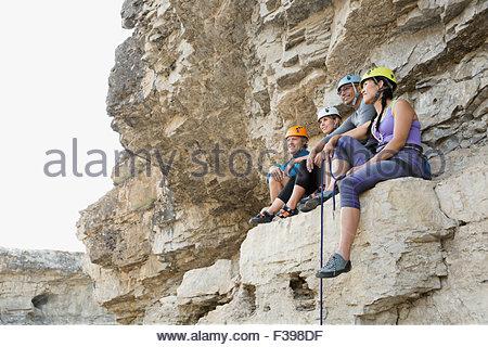 Rock climbers resting sitting on rock - Stock Photo