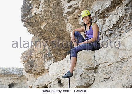 Portrait smiling female rock climber sitting on rock - Stock Photo