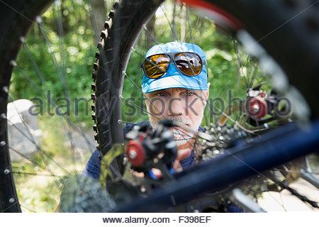 Close up senior man examining mountain bike wheel - Stock Photo