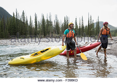 Couple with kayaks getting out of river - Stock Photo