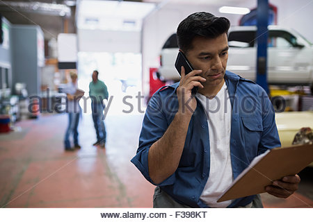 Mechanic with clipboard talking on cell phone - Stock Photo