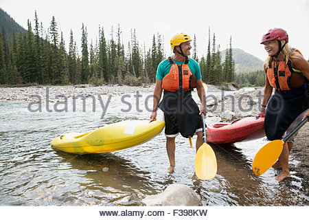 Smiling couple with kayaks in river - Stock Photo