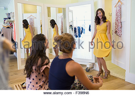 Woman trying on dress for friends clothing shop - Stock Photo
