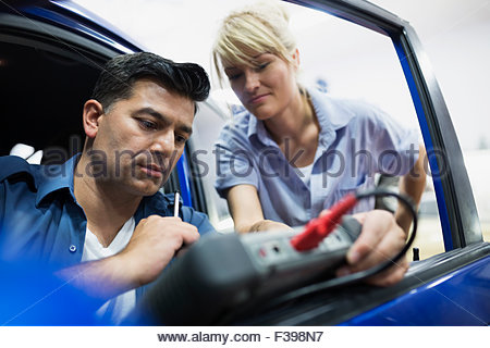Mechanics diagnostic testing car in auto repair shop - Stock Photo