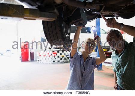 Female mechanic and customer underneath car - Stock Photo