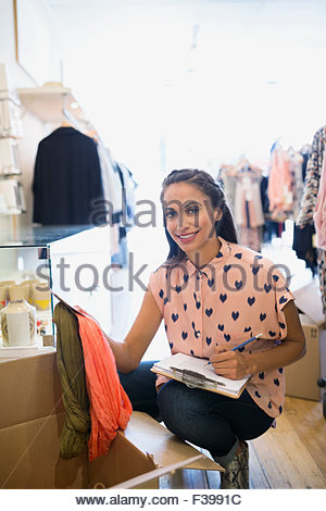 Portrait smiling business owner unpacking new inventory shop - Stock Photo