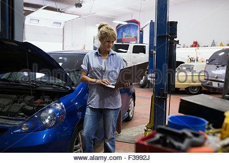 Female mechanic using laptop in auto repair shop - Stock Photo