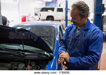 Mechanic looking down at engine auto repair shop - Stock Photo