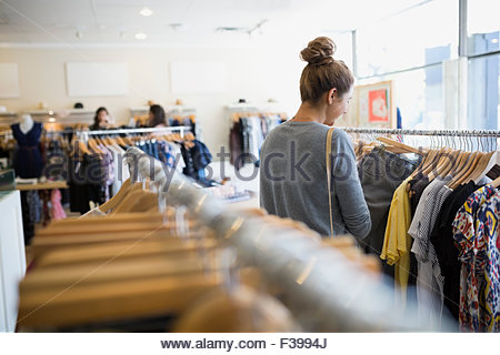 Woman browsing clothing rack in shop - Stock Photo