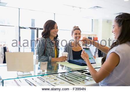 Worker swiping credit card reader digital tablet shop - Stock Photo