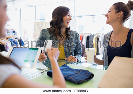 Laughing women paying at shop counter - Stock Photo